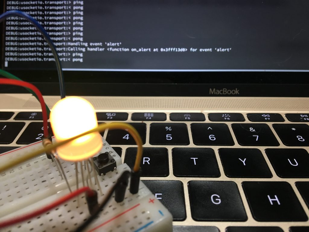 Electronics breadboard with a project on it sitting on a laptop keyboard
