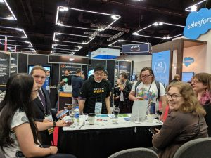 Photo of a six people at the Expo Hall at OSCON. One of them is wearing a suit.