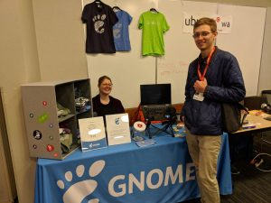 A photo of the GNOME booth at LFNW. Behind the booth sits one person, and another is standing in front of it. The table is blue.