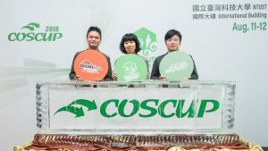 "A photo of three people, holding signs reading ""GNOME Asia,"" ""openSUSE,"" and ""COSCUP."""