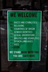 A sign that reads: We welcome all races and ethnicities all religions all countries of origin all gender identities all sexual orientations all abilities and disabilities all spoken lnguages all ages everyone. We stand here with you you are safe here