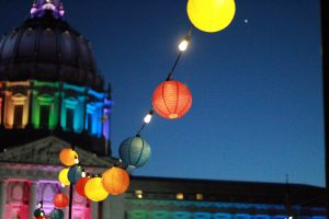A photo of spherical paper lanterns in a variety of colors, against a dark blue night sky. In the background is a building, lit in rainbow colors.