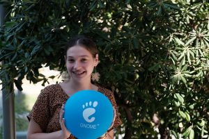 A photo of Kristi Progri, smiling and wearing fabulous flower earrings, in front of some trees. She is holding a blue balloon that has the GNOME logo on it.
