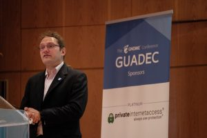 "A photo of Neil McGovern, Ecexutive Director of the GNOME Foundation in August 2019. He is wearing a suit. Behind him is a sign that says ""GUADEC"" and ""Private Internet Access."""
