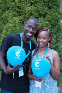 A photo of two smiling people standing in front of trees. The one on the left is wearing a black shirt, and the one on the right a blue dress. They are both holding a blue balloon with the GNOME logo on it.