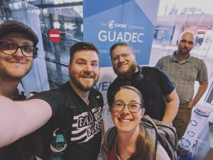 "A selfie of five people in front of a standee saying ""GUADEC"" at the Thessaloniki Airport."