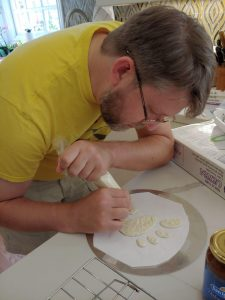 A man in a yellow shirt using an icing bag to pipe the GNOME logo in white.