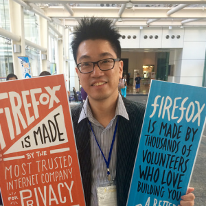 A photo of Sammy Fung holding up two firefox signs. He is wearing a suit jacket and a blue collared shirt. He has glasses and his hair is sticking up.