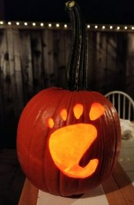 A jack-o-lantern: an orange pumpkin with a GNOME foot carved into it and candle light coming through the foot.