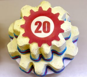 "A cake shaped like two gears with a red ""20"" printed on it."