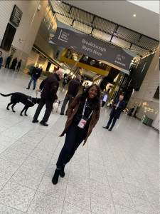 A photo of Regina, who is smartly dressed in black with a green jacket, standing in a conference center. Behind her is a man with a dog.