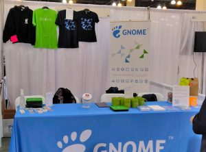 A photo of the GNOME booth, featuring a blue GNOME table cloth and exciting GNOME swag, including bugs, t-shirts, and a tote bag.