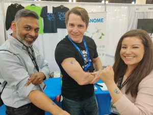 A photo of three people showing off temporary tattoos of the GNOME logo.