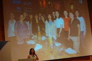 A photo of Marina Zhurakhinskaya in front of a photo of a group of women from the GNOME Women's Dinner.
